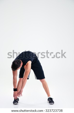 Full length portrait of athletic man doing warm up exercises isolated on a white background - stock photo