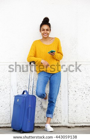Full length portrait of attractive african woman standing outside with suitcase and mobile phone - stock photo