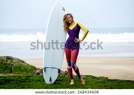 Full length portrait of attractive californian blond hair girl standing with her surfboard against ocean with beautiful waves on background - stock photo