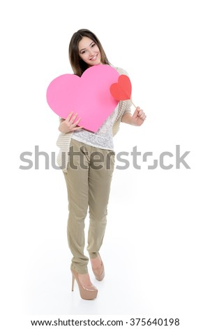 Full length portrait of attractive happy smiling teen girl with pink and red hearts, love holiday valentine symbol over white background