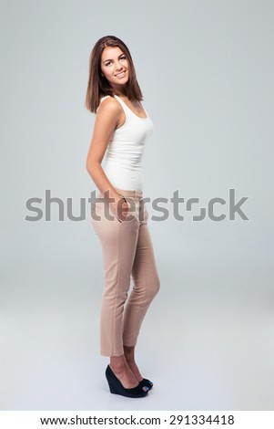 Full length portrait of attractive happy woman standing over gray background - stock photo