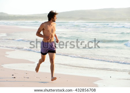 Full length portrait of attractive man running shirtless at the beach - stock photo