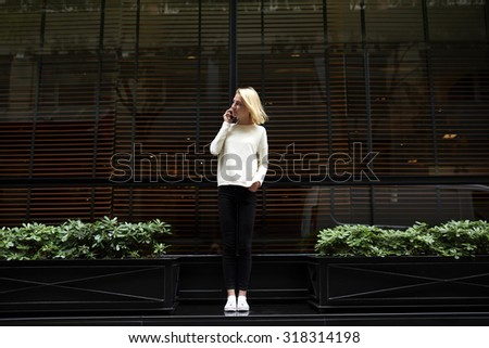 Full length portrait of attractive stylish female talking on smart phone while standing in urban setting on empty copy space background for your information content or text message,mobile conversation - stock photo
