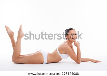 Full length portrait of attractive woman in white underwear lying with joy. She raises her legs and propping her head with her hand. She is smiling happily. Isolated on background - stock photo