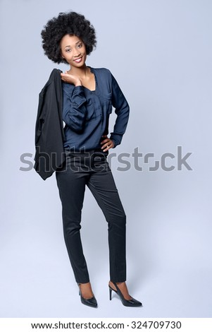Full length portrait  of attractive young black african model wears smart business suit in studio and smiling - stock photo