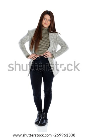 Full length portrait of attractive young girl posing in casuals with her hands on hips over white background - stock photo
