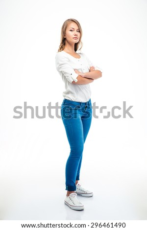 Full length portrait of attractive young woman standing with arms folded isolated on a white background - stock photo