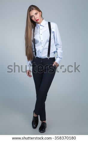 Full length portrait of beautiful business woman over light grey background. - stock photo