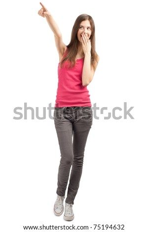 Full length portrait of beautiful casual girl pointing and looking surprised. Isolated on white background.