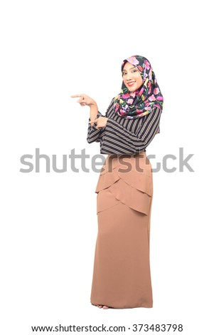 Full length portrait of beautiful casual girl pointing up and looking at camera. Isolated on white background. - stock photo