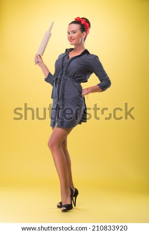 Full length portrait of beautiful sexy girl with pretty smile in pin-up style posing with rolling pin, sexy coquette in stockings, isolated on yellow