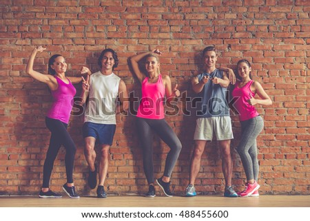Full length portrait of beautiful sports people gesturing, looking at camera and smiling, on brick wall background