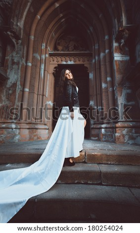 Full length portrait of beautiful woman in dress with long white veil walking on old stone stair - stock photo