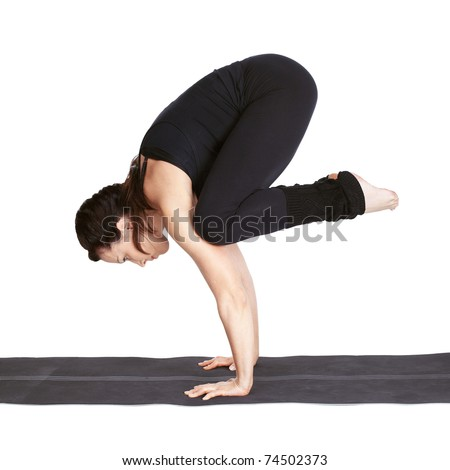 full-length portrait of beautiful woman working out yoga excercise bakasana (crane pose) on fitness mat - stock photo