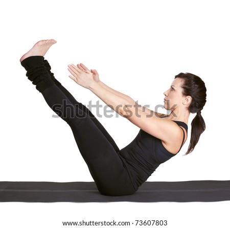 full-length portrait of beautiful woman working out yoga excercise paripurna navasana (full boat pose) on fitness mat - stock photo