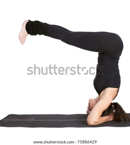 full-length portrait of beautiful woman working out yoga excercise salamba sirsasana (supported head stand) on fitness mat - stock photo