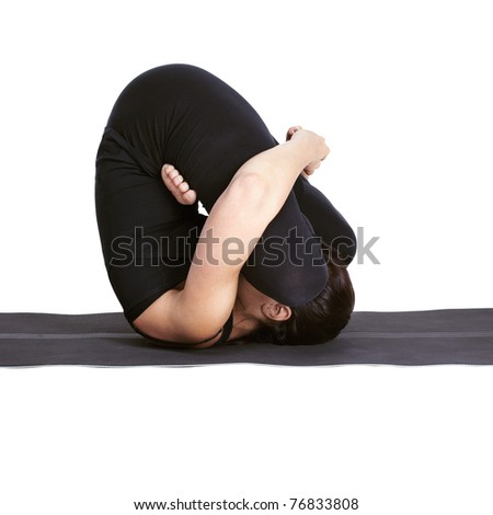 full-length portrait of beautiful woman working out yoga excercises pindasana pose on fitness mat - stock photo