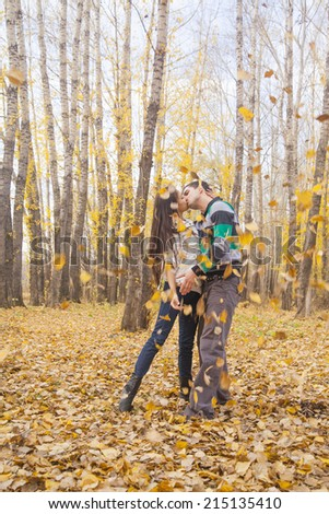 Full length portrait of beautiful young adult latin hispanic pair or couple standing, embracing and kissing in yellow autumn park background Empty copy space for inscription