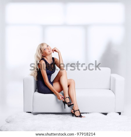 full-length portrait of beautiful young blond woman on couch checking court shoe fastener - stock photo