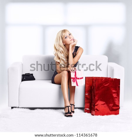 full-length portrait of beautiful young blond woman on couch with shopping bags and gift in hands