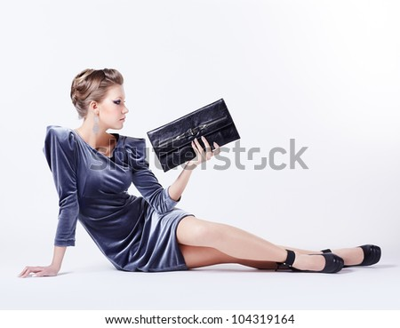 full-length portrait of beautiful young brunette woman in fancy dress and court shoes sitting on the floor with clutch in hand - stock photo