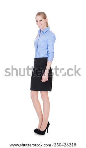 Full length portrait of beautiful young businesswoman standing over white background - stock photo