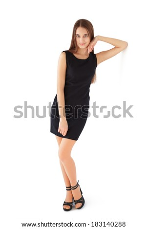 Full length portrait of beautiful young smiling woman in black dress leaning against wall isolated on white background - stock photo