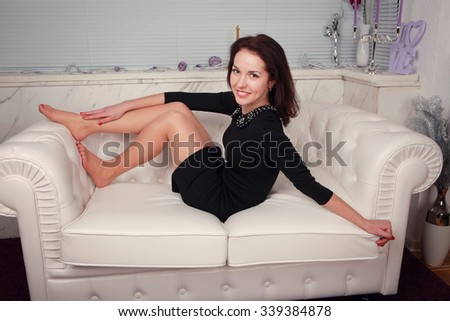 full-length portrait of beautiful young  woman on couch   - stock photo