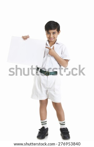 Full length portrait of boy in school uniform showing blank placard against white background - stock photo