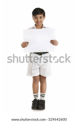 Full length portrait of boy in school uniform showing blank placard over white background - stock photo