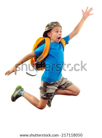 Full length portrait of boy with backpack and  cap running, jumping and  waving with his hand and shouting.   - stock photo