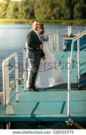 Full length portrait of bride and groom hugging on pier on river - stock photo