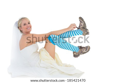 Full length portrait of bride wearing sports shoes over white background