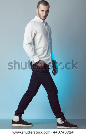 Full length portrait of brutal young man with short hair, bristle on face wearing white shirt, blue jeans, sneakers, walking over gray background. Street style. Studio shot
