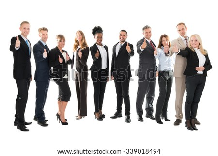 Full length portrait of business team showing thumbs up against white background - stock photo