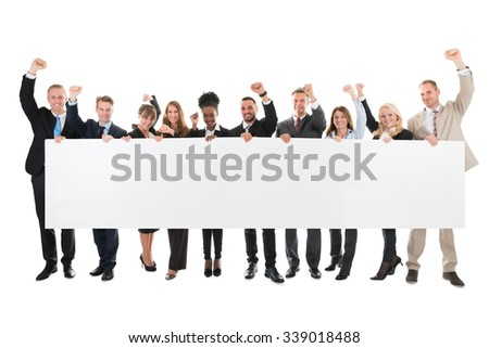 Full length portrait of business team with arms raised holding blank billboard against white background - stock photo