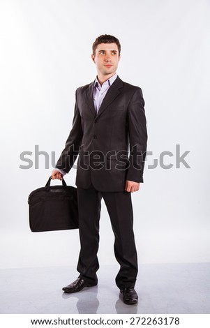 Full-length portrait of businessman handing briefcase, isolated on white. Concept of business and success - stock photo