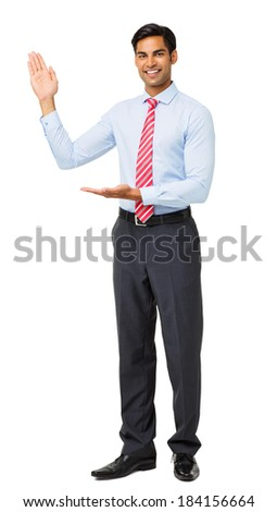 Full length portrait of businessman presenting an invisible product against white background. Vertical shot. - stock photo
