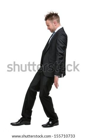 Full-length portrait of businessman setting against something who wears suit with blue tie, isolated on white