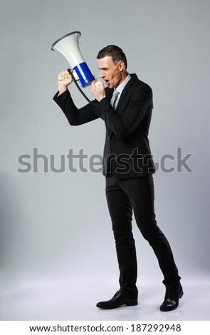 Full length portrait of businessman yelling through megaphone on gray background - stock photo