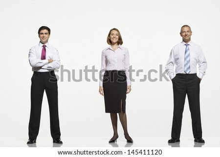 Full length portrait of businesspeople standing side by side against white background - stock photo
