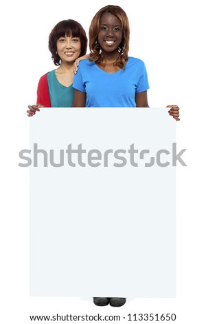 Full length portrait of casual girls standing behind blank whiteboard - stock photo