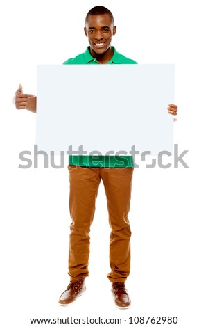 Full length portrait of casual young guy pointing towards placard