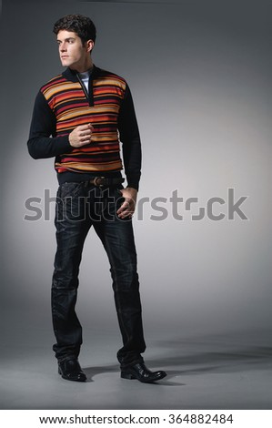full length portrait of casual young man, standing on light background - stock photo