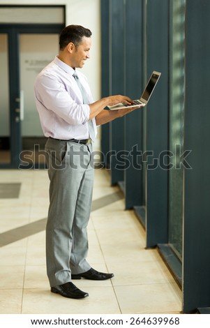 full length portrait of caucasian businessman using laptop computer - stock photo