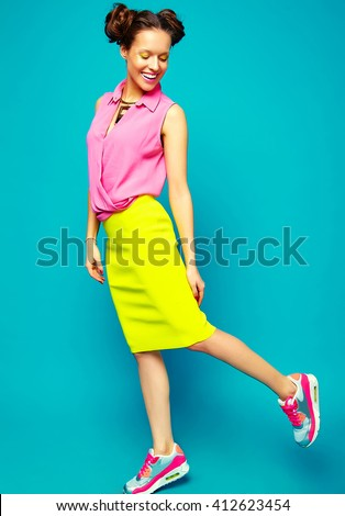 full length portrait of cheerful  fashion hipster girl in casual colorful vivid hipster blue and pink summer clothes on blue background with toy in hands - stock photo
