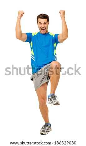 Full length portrait of cheerful young man in sportswear celebrating over white background. Vertical shot.