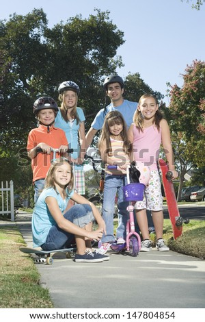 Full length portrait of children with scooters and skateboard