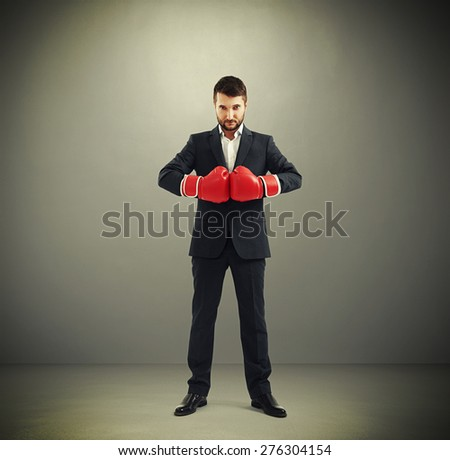 full length portrait of confided businessman in red boxing gloves looking at camera over dark background - stock photo