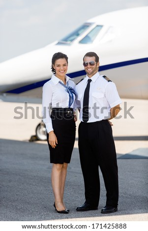 Full length portrait of confident airhostess and pilot standing against private jet at terminal - stock photo